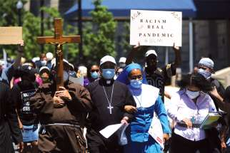 Washington Auxiliary Bishop Roy E. Campbell and a woman religious walk with others toward the National Museum of African American History and Culture during a protest June 8, following the death of George Floyd.