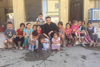 The Rev. Martin Banni with a group of displaced children from the Christian towns in Nineveh in Irbil. Banni spent much time playing with children and telling them stories from the Bible.
