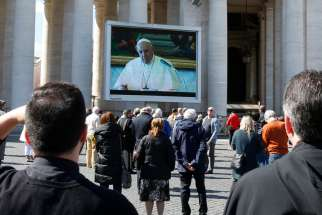 "Pope Francis is pictured on a video monitor in St. Peter's Square as he leads the Angelus from his library in the Apostolic Palace at the Vatican March 8, 2020. As a precaution to avoid spread of the coronavirus, the pope's Sunday Angelus was broadcast on television and displayed on monitors in St. Peter's Square. After leading the Angelus through video the pope said he wanted to see the crowd in ""real time"" and came to the window of his studio to greet people in the square."