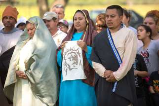Catholics in Fresno, dressed in costume, participate in a Good Friday presentation of the Way of the Cross April 3, 2015. The tradition of a living Stations of the Cross is especially strong in the diocese's migrant communities.