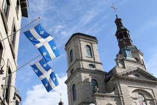 Quebec provincial flags are displayed outside a building across the street from the Cathedral-Basilica of Notre-Dame de Quebec in Quebec City Oct. 5.