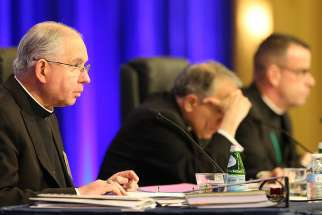 Archbishop Jose H. Gomez of Los Angeles, vice president of the U.S. Conference of Catholic Bishops, gives the opening prayer Nov. 13 at the bishops' fall general assembly in Baltimore. Also pictured are Cardinal Daniel N. DiNardo of Galveston-Houston, USCCB president, and Msgr. J. Brian Bransfield, USCCB general secretary.
