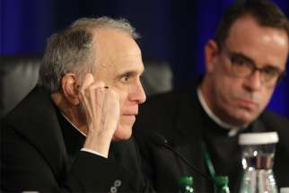 Cardinal Daniel N. DiNardo of Galveston-Houston, president of the U.S. Conference of Catholic Bishops, looks on at the conclusion of the second day of the spring general assembly of the USCCB in Baltimore June 12, 2019. Looking on is Msgr. J. Brian Bransfield, general secretary.
