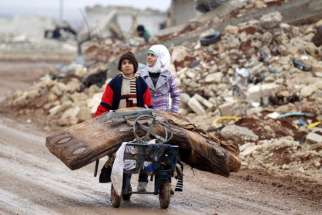 Syrian children transport their salvaged belongings from their damaged house in Doudyan, a village in northern Aleppo, Jan. 2.