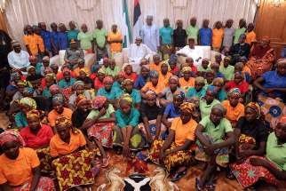 A group of Chibok girls are seen with Nigerian President Muhammadu Buhari in Abuja, Nigeria, May 7. The girls were held captive for three years by Boko Haram militants.