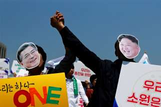 People hold hands and wear masks of South Korean President Moon Jae-in and North Korean leader Kim Jong Un during a unification rally in Seoul, South Korea, April 25.