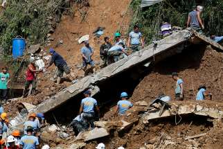 Rescue workers and volunteers search for buried villagers Sept. 16 after Typhoon Mangkhut hit Itogon, Philippines. Villagers had taken shelter in an abandoned mine shaft that collapsed.