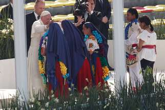 Pope Francis greets girls in traditional dress during a meeting with young people at the Jose Maria Morelos Pavon Stadium in Morelia, Mexico, Feb. 16.