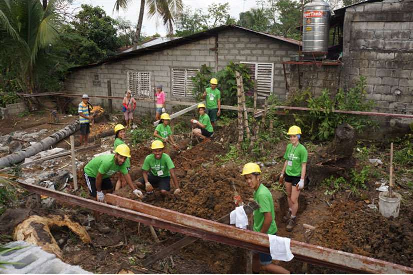 Above, volunteers are digging out the foundation for a new home.