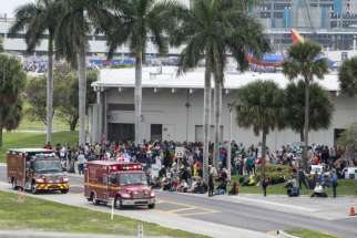 Firemen and ambulances wait outside Fort Lauderdale's airport in Florida Jan. 7, after a gunman opened fire killing at least five people and injuring eight more. Olga Woltering of Transfiguration Catholic Church in Marietta, Ga., was one of the victims killed in the shooting.
