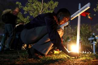 "A woman lights a candle on a wooden cross after an April 14 memorial concert in Nairobi, Kenya, for the 147 people killed in an attack on Garissa University College. Pope Francis is calling for perpetrators of extremist violence in Kenya ""to come to their senses and seek mercy."""