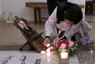 A nun lights a candle next to a photograph of Bishop Pierre Claverie at his grave in St. Mary's Cathedral, where a vigil was held in Oran, Algeria, Dec. 7