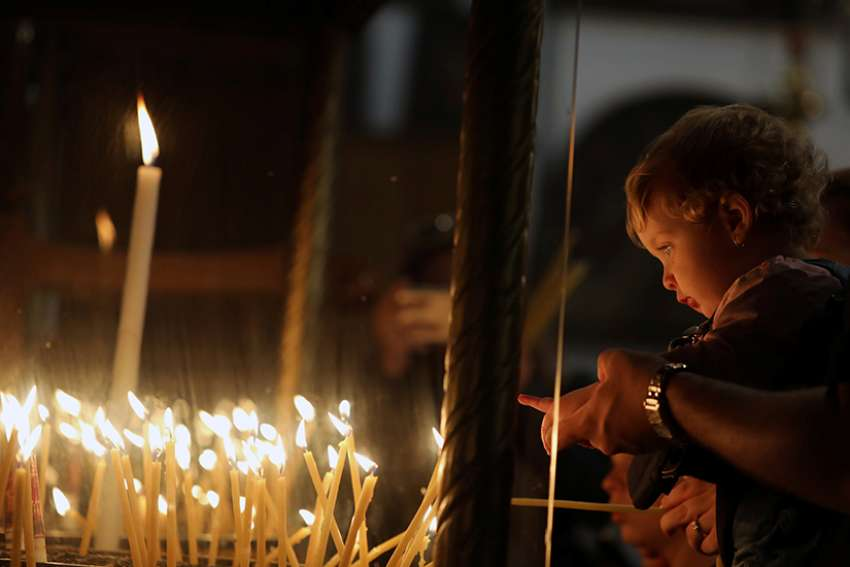 A child points at candles Dec. 19 in the Church of the Nativity, where tradition holds Christ was born, in Bethlehem, West Bank.