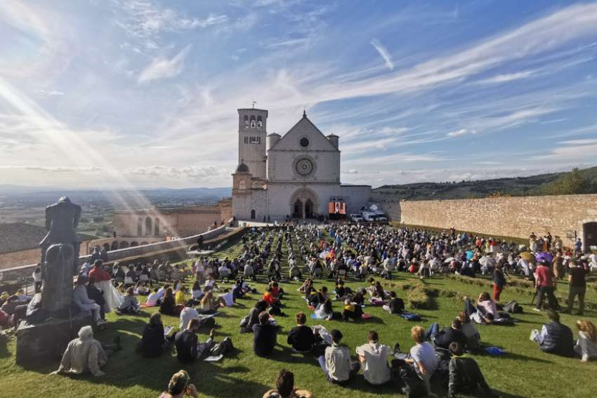 People sit outside the Basilica of St. Francis in Assisi as they attend the beatification Mass of Carlo Acutis in Assisi, Italy, Oct. 10, 2020. The Mass was held inside the basilica but measures to prevent the spread of COVID-19 meant that most of the attendees sat outside.