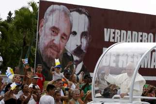Pope Francis waves to people as he passes a billboard showing images of Cuba's former leader Fidel Castro and Cuban independence hero Jose Marti Sept. 19 in Havana.