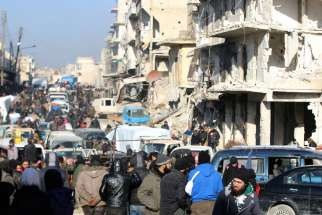 People wait near damaged buildings to be evacuated Dec.19 from Aleppo, Syria.