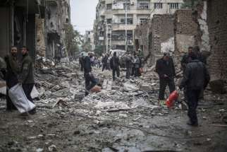 "Syrians look at a destroyed field hospital in the rebel-held area of Douma on the outskirts of Damascus, Oct. 29, 2015. Christian patriarchs residing in Damascus urged the international community to ""stop the siege of the Syrian people"" and to lift international sanctions, which they say are deepening the suffering."