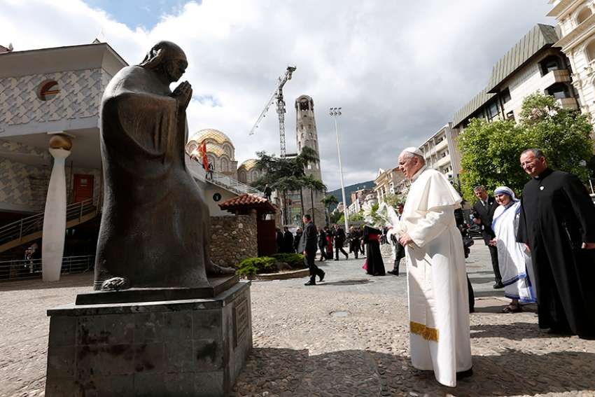 Pope Francis prepares to place flowers at a statue of Mother Teresa at the Mother Teresa Memorial during a meeting with religious leaders and the poor in Skopje, North Macedonia, May 7, 2019.