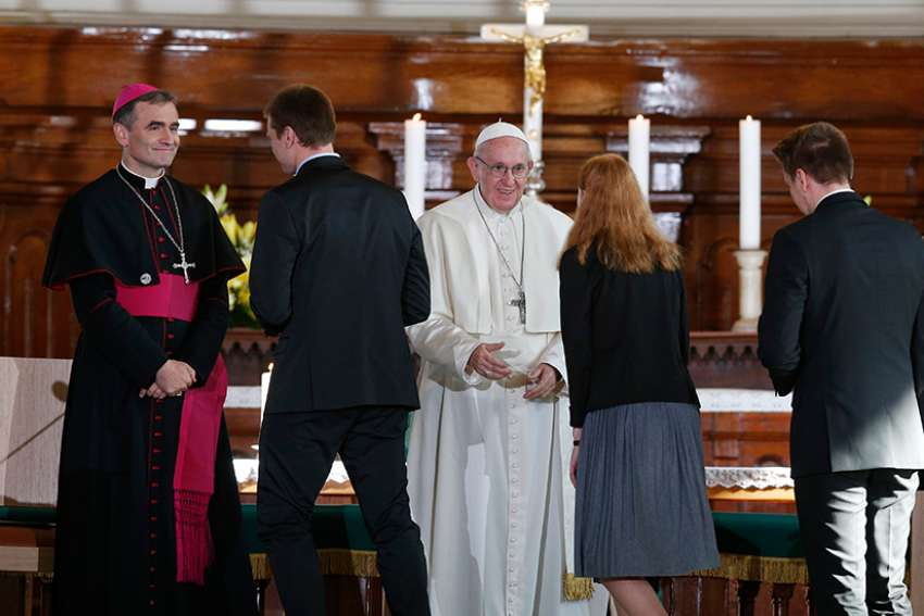 Pope Francis greets a young woman during an ecumenical encounter with young people at the Kaarli Lutheran Church in Tallinn, Estonia, Sept. 25.