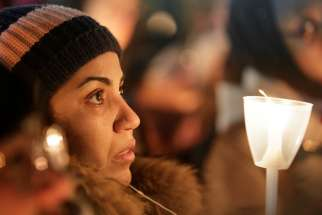 A woman becomes emotional during a Jan. 30 vigil in support of the Muslim community in Montreal. A lone gunman entered the Quebec Islamic Cultural Centre and opened fire Jan. 29, killing at least six men who were praying and injuring 19 more.