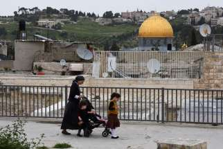 An Orthodox Jewish woman walks with her children on the roof in the Arab section of the Old City of Jerusalem on her way from an Israeli settlement March 26. The Jewish settlement is near the Church of the Holy Sepulcher and the Church of the Redeemer in the Christian Quarter of the Old City.