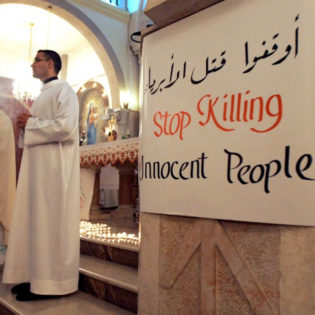 A sign in response to the violence in Syria is seen during a Feb. 11 Mass at a church in the West Bank town of Ramallah. As a sectarian conflict in Syria intensified, Pope Benedict XVI called on all Syrians to begin a process of dialogue and reminded the government of its duty to recognize its citizens' legitimate demands.