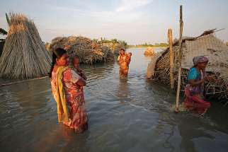 Women carry children as they make their way through a flooded area Aug. 20 in Bogra, Bangladesh.