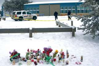 A makeshift memorial is seen Jan. 25 near a Royal Canadian Mounted Police vehicle parked outside La Loche Community School in La Loche, Sask. Police charged a 17-year-old young man with four counts of first-degree murder and seven counts of attempted murder in the Jan. 22 mass shooting at the school and a nearby home.