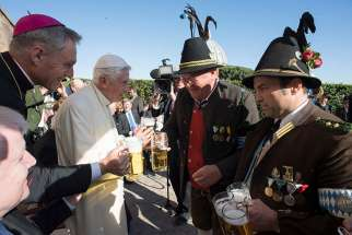Retired Pope Benedict XVI and Archbishop Georg Ganswein, prefect of the papal household, left, toast men in traditional clothing with a beer during the German pontiff's 90th birthday celebration April 17 at the Vatican. The pope's birthday was the previous day.