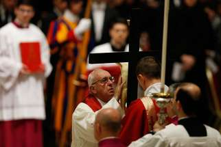 Pope Francis reverences the crucifix during the Good Friday service in St. Peter's Basilica at the Vatican March 25.