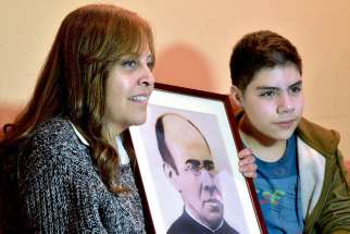 Veronica Stoberg of Santiago, Chile, alongside her son, Sebastian, holds a photo May 12 of Blessed Faustino Miguez, who is credited with her miraculous recovery after a complicated childbirth. The Spanish priest will be canonized by Pope Francis in October.