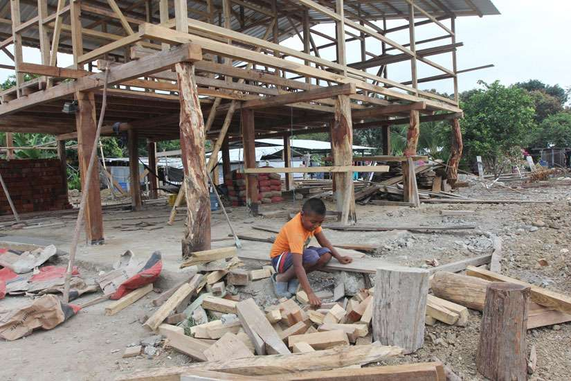A boy sorts through pieces of wood outside a house being rebuilt in the village of Bigua, Ecuador July 27. Although reconstruction is under way, many families continue to live in tents provided by Catholic Relief Services and Caritas Internationalis.