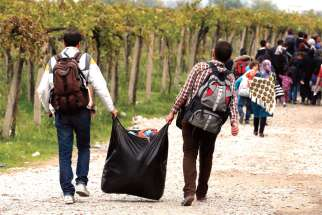 Refugees carry their belongings in Macedonia after crossing from a transit camp in Idomeni, Greece, Oct. 19. A new endowment has been set up to help refugees settle in Toronto.