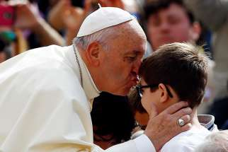 Pope Francis kisses a child during his general audience in St. Peter's Square at the Vatican May 2.
