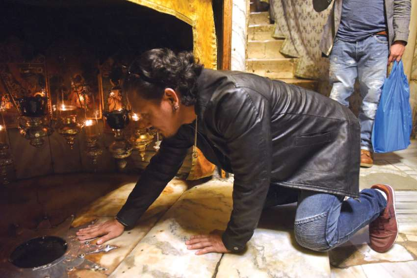 A tourist prays in the grotto of the Church of the Nativity, touching the silver star that marks the site where Christ was born, in Bethlehem.