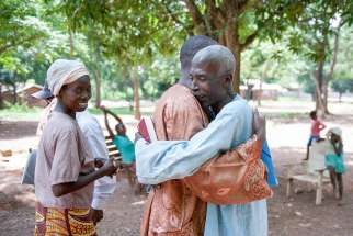 Villagers embrace in 2014 on the grounds of the Monastery of Boy Rabe in Bangui, Central African Republic.