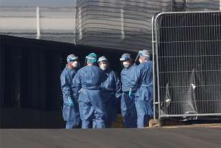 Medical staff are seen wearing protective clothing outside the Nightingale Hospital in London April 9, 2020. The Bishops' Conference of England and Wales recommended that, because of the lack of personal protective equipment, during the COVID-19 pandemic priests should counsel patients by telephone rather than give them last rites.