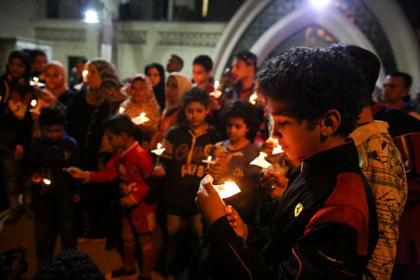 A boy holds a candle during an April 9 candlelight vigil for the victims of a bomb explosion at the Orthodox Church of St. George in Tanta, Egypt. Pope Francis said in a video message April 25 that he hopes his trip to Egypt will be a sign of friendship and peace.