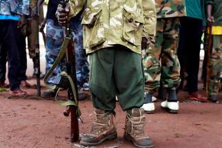 "In this file photo, a former child soldier in Yambio, South Sudan, holds a gun during a child soldiers' release ceremony. Catholic bishops in South Sudan and Sudan appealed to the citizens of the two countries to work harder for peace, telling them, ""True peace can only be built by citizens like you."""