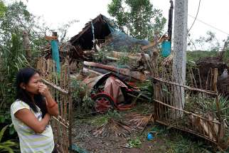 A woman in Bangui, Philippines, stands outside her house damaged by a fallen tree Oct. 20 after Typhoon Haima hit. Typhoon Nock-Ten hit the country Christmas Day.