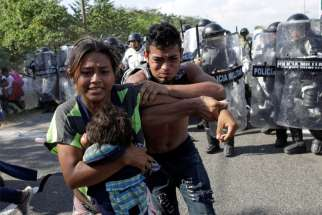 Migrants from Central America trying to reach the United States react as police approach them near Frontera Hidalgo, Mexico, Jan. 21, 2020. At least 138 Salvadorans have been murdered after being deported back to country from the United States, according to a report released Feb. 5 from Human Rights Watch.