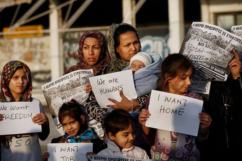 Afghan women hold placards as they take part in a protest demanding better living conditions at the refugee camp of the former international Helliniko airport in Athens, Greece, Feb. 18, 2017.
