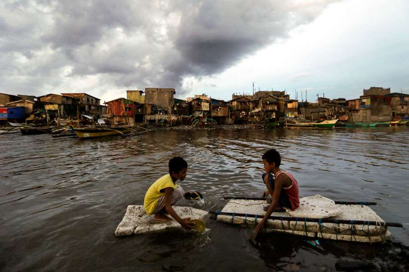 Children paddle in water in Navotas City, Philippines, May 10.