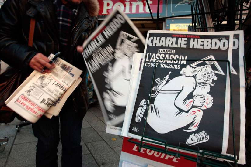 "A man takes a copy of the latest edition of the French weekly Charlie Hebdo with the title ""One year on, The assassin still on the run"" displayed at a kiosk in Nice, France, on Jan. 6, 2016. France this week commemorates the victims of last year's Islamist militant attacks on the satirical publication and a Jewish supermarket with eulogies, memorial plaques and another cartoon lampooning religion."