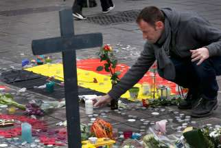 A man places flowers on a street memorial March 23 following bomb attacks in Brussels. Three nearly simultaneous attacks March 22 claimed the lives of dozens and injured more than 200.