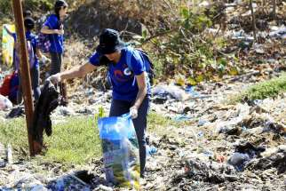 "A volunteer picks up trash at Freedom Island, a marshland considered to be a sanctuary for birds, fish and mangroves in a coastal area of Las Pinas City, near Manila, Philippines, April 22, 2015. Catholic bishops in the Philippines criticized ""the continuing destruction of our common home"" and called for ""ecological conversion"" amid ""climate emergency."""