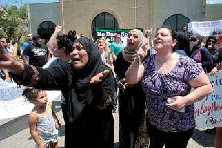 Women react as they talk about family members who were arrested by immigration officials during a June 12 rally outside the Mother of God Chaldean Catholic Church in Southfield, Mich. Dozens of Chaldean Christians were arrested by federal immigration officials over the weekend of June 10 and 11 in the Detroit metropolitan area, which members of the local church community said left them feeling sad and frustrated.