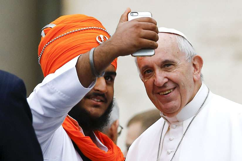 Pope Francis poses for a selfie with a member of the inter-religious community during his weekly audience in St. Peter's Square at the Vatican Oct. 28.