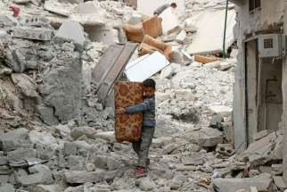 A boy carries belongings Nov. 17 as he walks on the rubble of damaged buildings in Aleppo, Syria.
