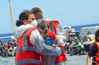 Volunteers of the Order of Malta's Italian Relief Corps provide assistant to an infant rescued in the Mediterranean Sea. Since 2007, the order's relief corps has worked alongside the Italian coast guard rescuing refugees stranded in the Mediterranean Sea.